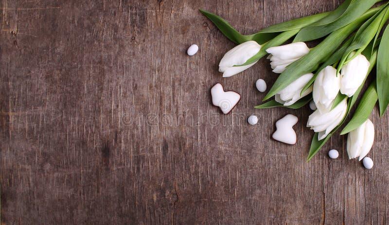 Cukierki dla świętują wielkanoc Biali tulipany, czekoladowi jajka i królik, fotografia stock