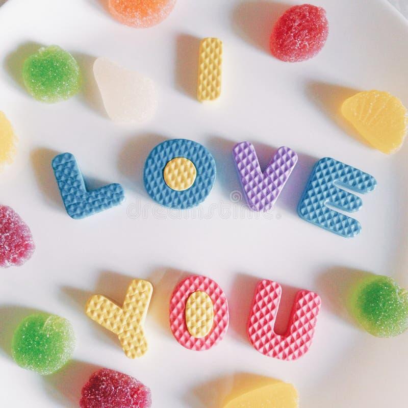 Cukierki i inskrypcja kocham ciebie czerwona róża zdjęcie stock