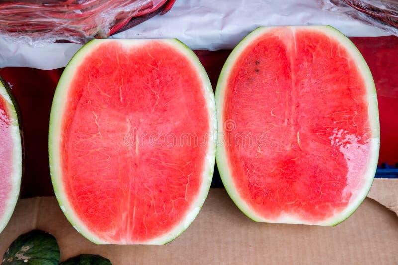 Cukierki wodny melon, niektóre ciie połówkę Arbuz przy rynkiem Świezi organicznie arbuzy na rynku zdjęcia royalty free