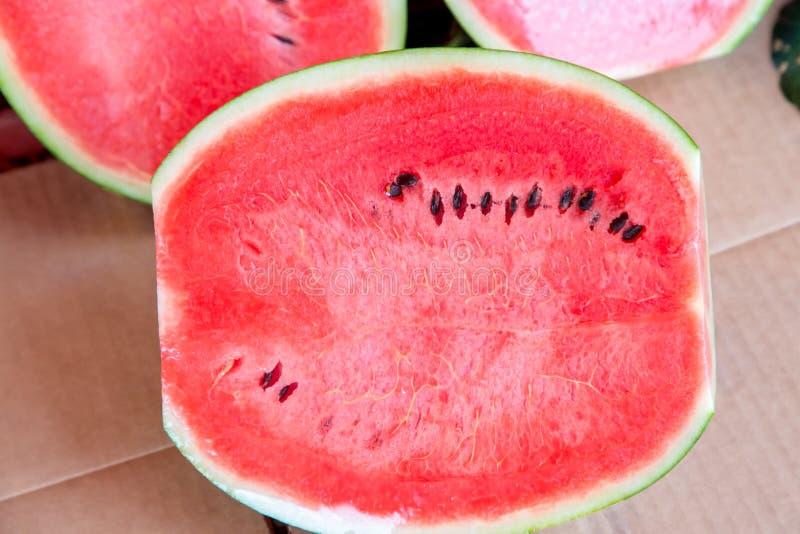 Cukierki wodny melon, niektóre ciie połówkę Arbuz przy rynkiem Świezi organicznie arbuzy na rynku zdjęcie royalty free