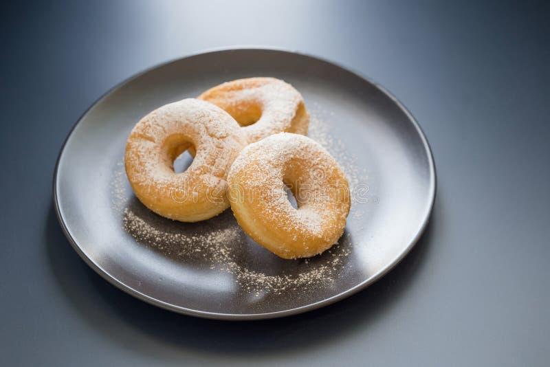 Cukierkowy pączek na czarnym talerzu na ciemnym stołowym tle w w fotografia stock
