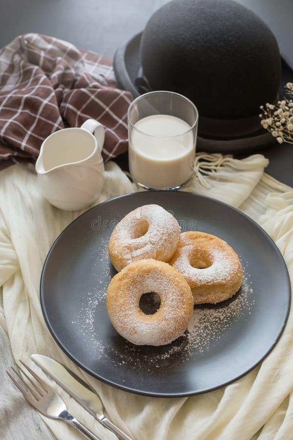 Cukierkowy pączek na czarnym talerzu szkle mleko na ciemnym stole i zdjęcia royalty free
