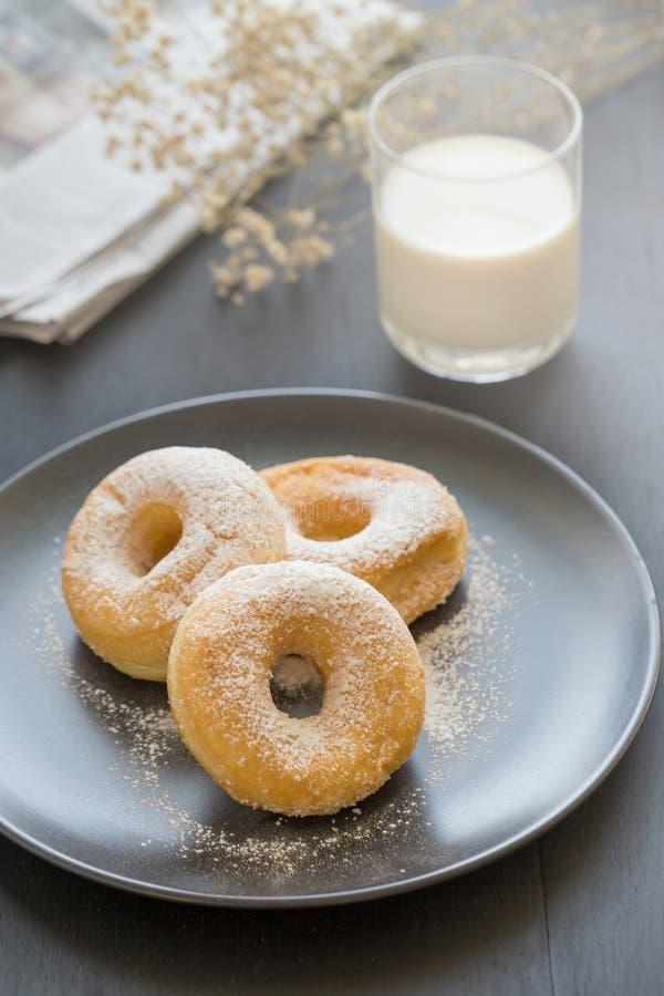 Cukierkowy pączek na czarnym talerzu szkle mleko na ciemnym stole i zdjęcia stock