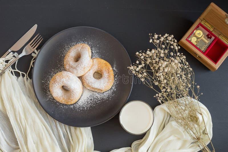 Cukierkowy pączek na czarnym talerzu szkle mleko na ciemnym stole i obraz royalty free