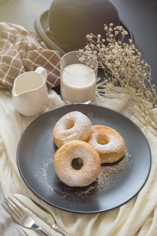 Cukierkowy pączek na czarnym talerzu szkle mleko na ciemnym stole i obrazy royalty free