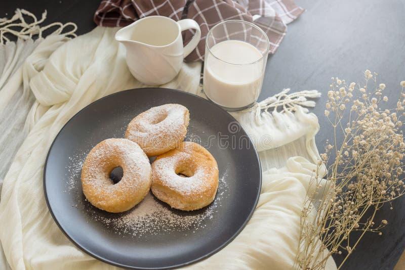 Cukierkowy pączek na czarnym talerzu szkle mleko na ciemnym stole i obraz stock