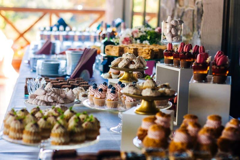 Cukierku bar Stół z różnymi tortami, cukierkami i deserami dla przyjęcia, zdjęcie royalty free
