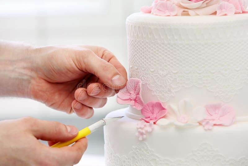 Cukierniczka dekoruje białego ślubnego tort zdjęcia stock