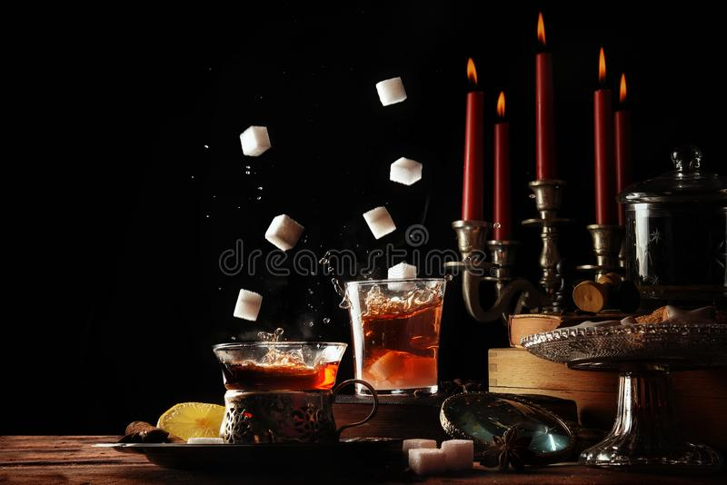 Cukrowi sześciany spada w teacups szkło na wieśniaka stołu położeniu z świeczkami i cukierkami, wygodna słodka przerwa w ciemnej  zdjęcie stock