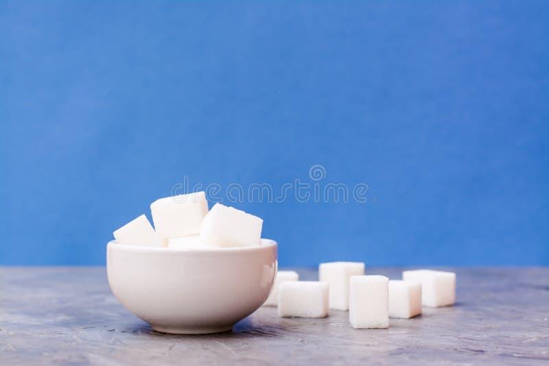 Cukrowi sześciany w białym pucharze obok stołu i obrazy stock