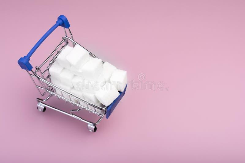Cukrowi sze?ciany Wózek na zakupy z pisze cukrowych sześcianach odizolowywających na różowym tle Cukrowy poj?cie Odg?rny widok obrazy stock