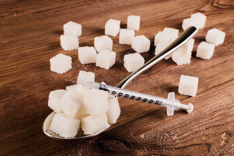 Cukrzyce Mnóstwo cukrowi sześciany w łyżce i inżektorze zdjęcie stock