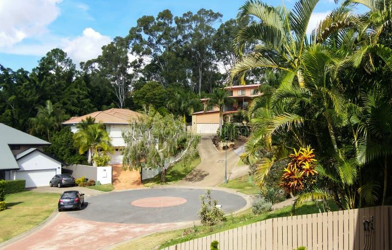 Cul-de-sac dans la banlieue d'Australie du Queensland avec des maisons sur des collines avec les allées raides et les arbres de g photo libre de droits