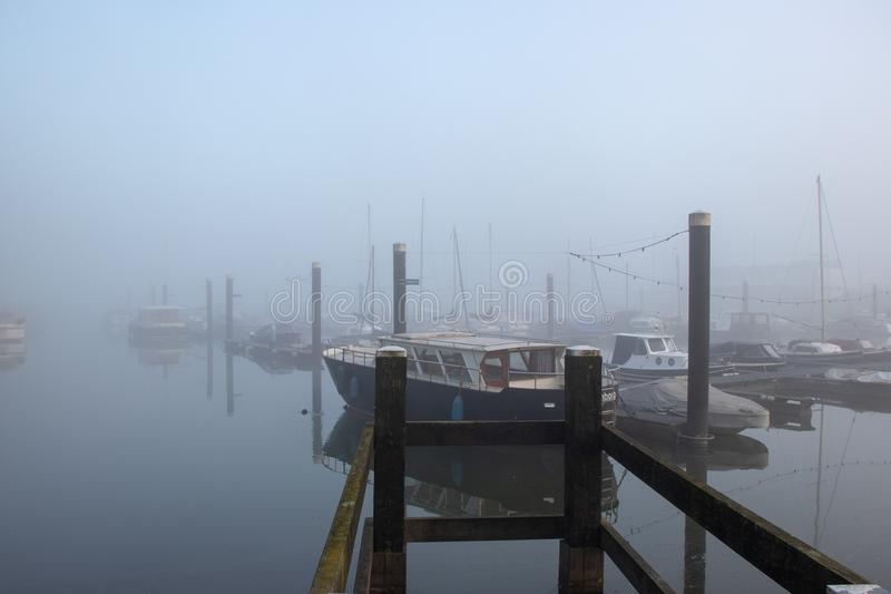 Culemborg, fog in the harbour. A foggy morning in the harbour of Culemborg in the Netherlands. Boats are moored on the docks royalty free stock image