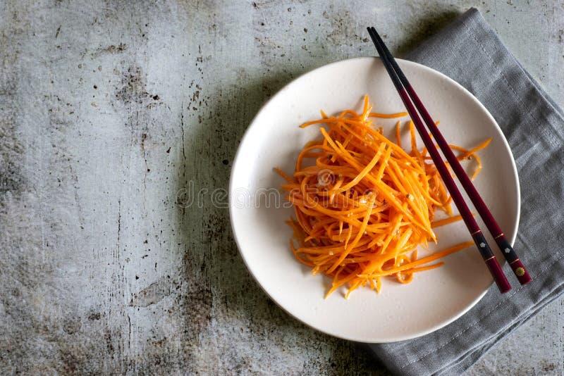 Culinária coreana: petisco picante da cenoura com alho e pimenta em uma placa agradável com hashis e um guardanapo cinzento em um fotografia de stock royalty free