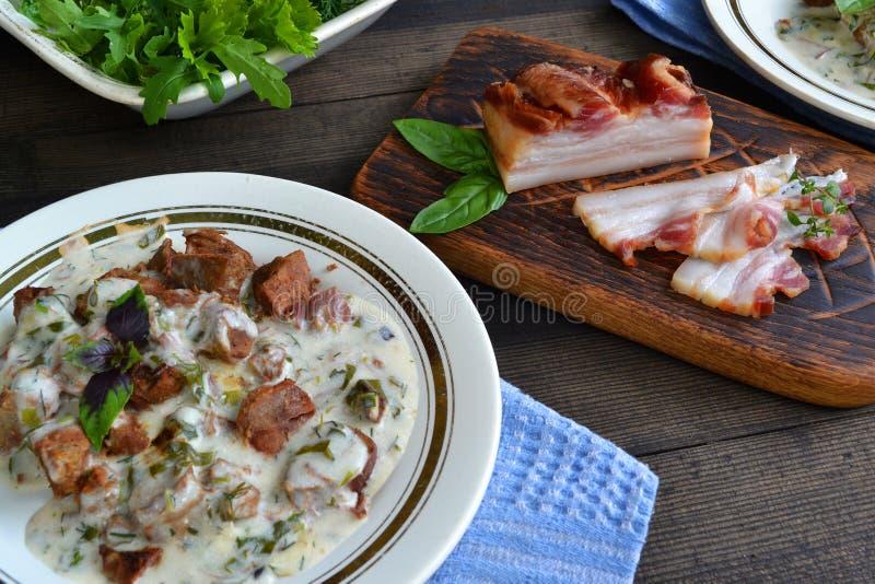 Culinária do russo: carne da carne do close up cozido com os vegetais no potenciômetro cerâmico no fundo de madeira imagens de stock