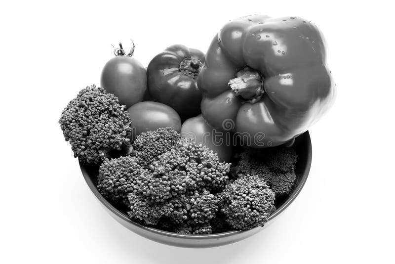 Culinária e conceito da dieta do vegetariano Brócolis, tomates vermelhos e amarelos e pimentas de sino na placa imagem de stock