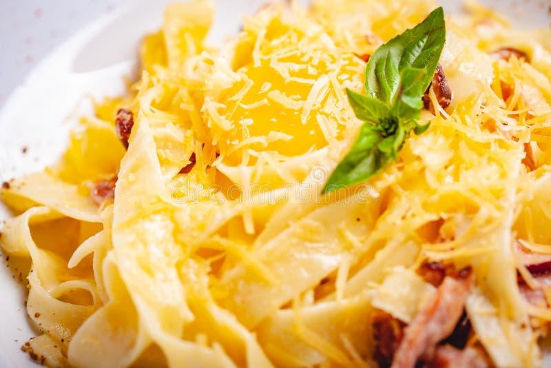 Culinária italiana Carbonara da massa com bacon, queijo e ovo na placa branca fotografia de stock