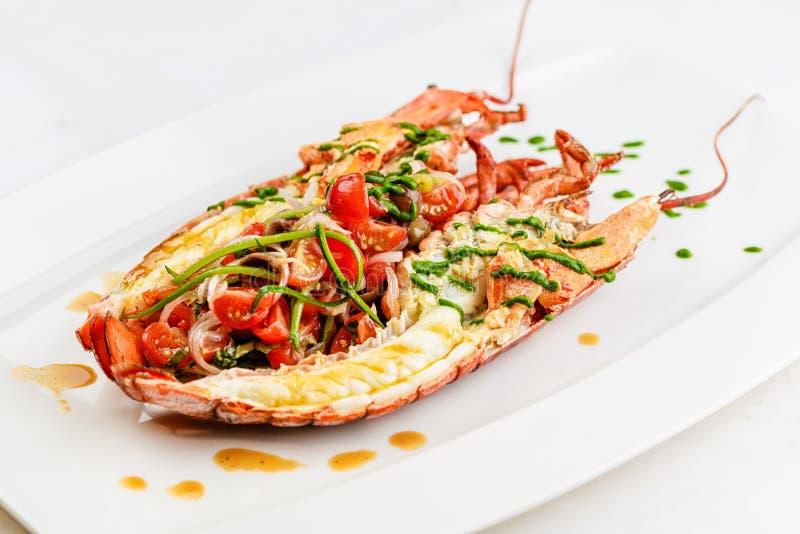 Culinária italiana A lagosta inteira cozida e cortada ao meio serviu com salada e molho do tomate na placa branca foto de stock