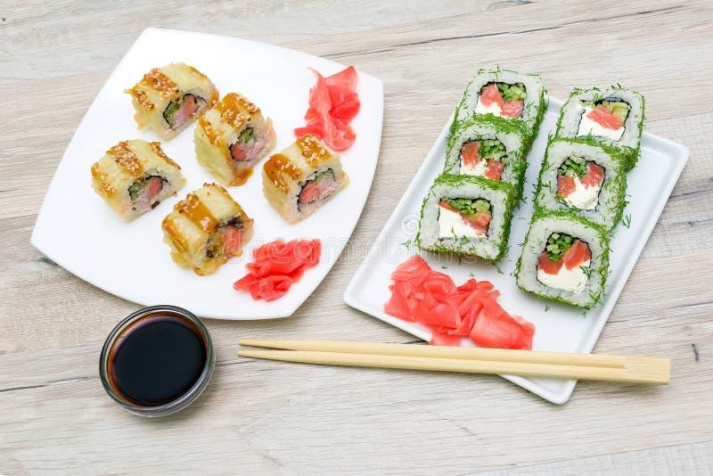 Culinária japonesa - rolos diferentes na placa em um tabl de madeira foto de stock