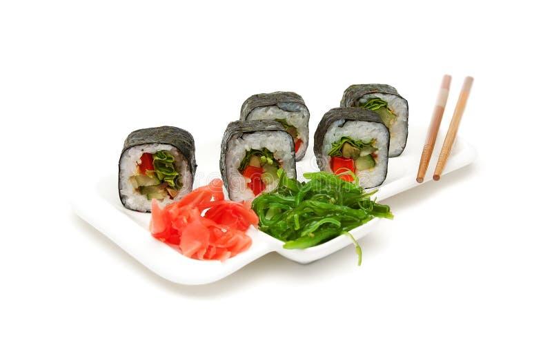 Culinária japonesa: rolos em uma placa em um fundo branco fotografia de stock royalty free