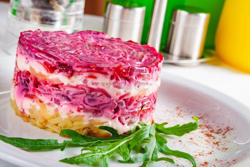 Culinária russian tradicional Arenques da salada sob o casaco de pele na placa branca imagem de stock royalty free
