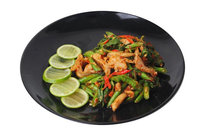 A culinária tailandesa, a ervilha fritada picante e a manjericão com carne de porco cobriram o limão verde cortado na placa preta imagem de stock royalty free