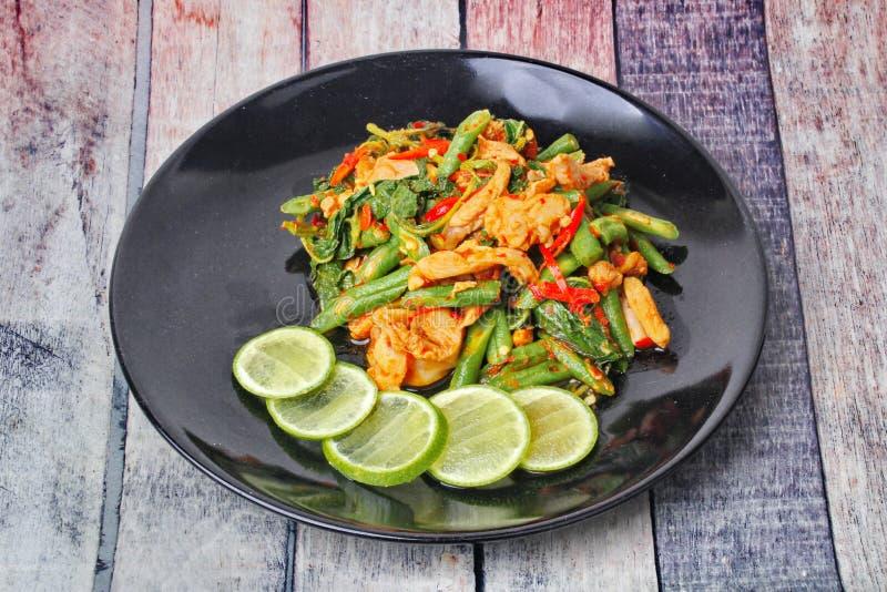 A culinária tailandesa, a ervilha fritada picante e a manjericão com carne de porco cobriram o limão verde cortado na placa preta foto de stock royalty free