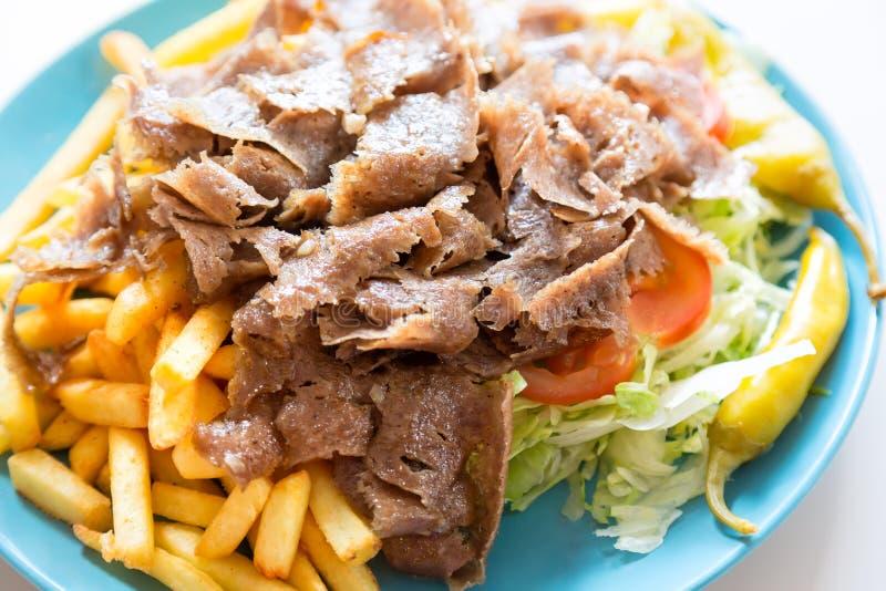 Culinária turca Carne do no espeto de Doner com as batatas e a salada dos frites dos pommes na placa Feche acima com foco seletiv imagem de stock