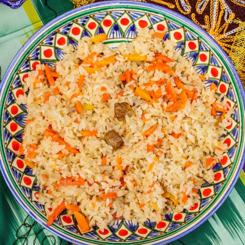 Culin?ria oriental Pilau do Uzbeque ou plov do arroz e da carne em uma placa com um teste padrão étnico fotos de stock royalty free