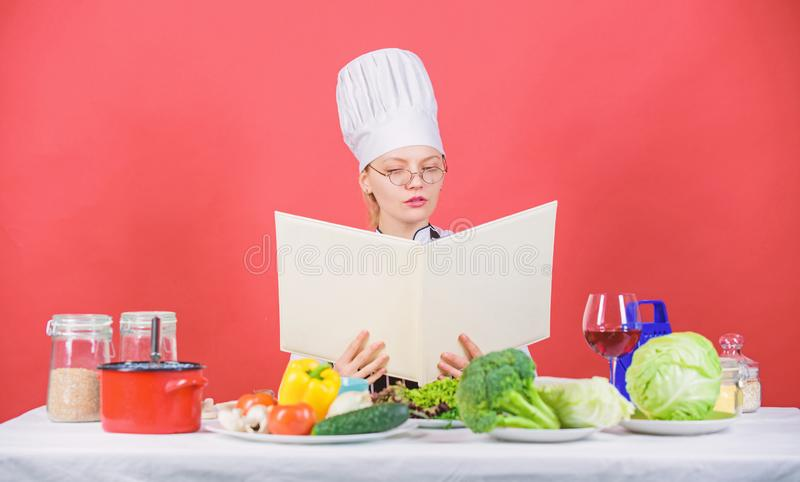 Culinair schoolconcept Het wijfje in hoed en schort kent alles over culinaire arts. Culinaire deskundige Vrouwenchef-kok stock afbeeldingen
