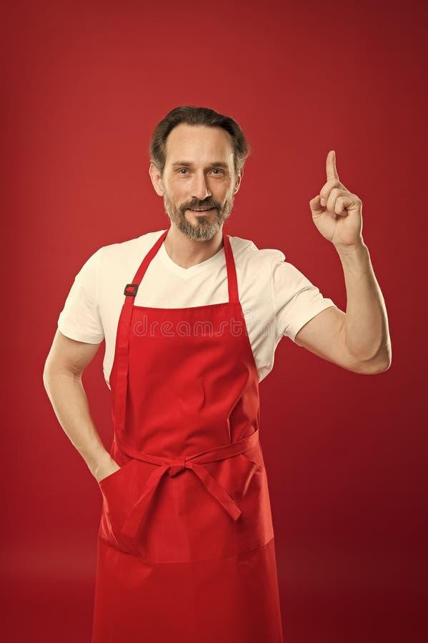Culinaire magisch Kok met baard en snor die schort rode achtergrond dragen Stellende kokende schort van de mensen de rijpe kok le royalty-vrije stock foto