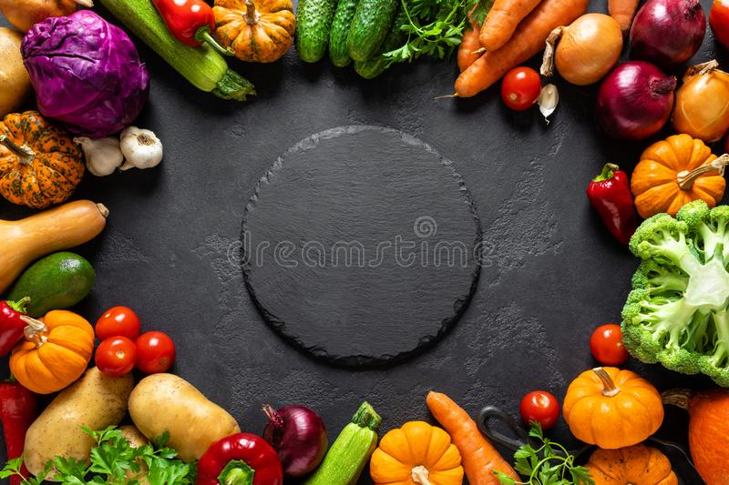 Culinary background with fresh raw vegetables on a black kitchen table, healthy vegetarian food concept, flat lay composition. Top view stock photos