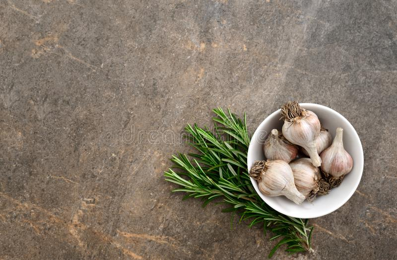 Culinary background with rosemary and garlic stock photo