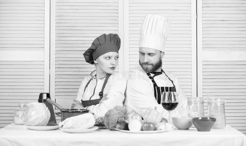 Culinary battle concept. Woman and bearded man culinary show competitors. Who cook better. Ultimate cooking challenge. Culinary battle of two chefs. Couple stock image