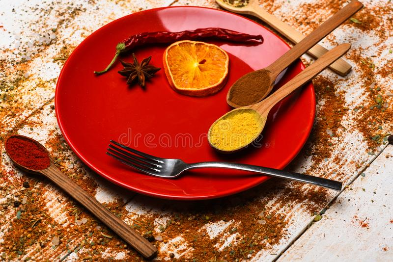 Culinary concept. Spices as grinded red pepper and curcuma powder scattered. Plate and fork with dried orange and chilly royalty free stock photography
