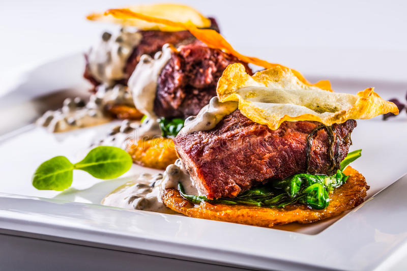 Culinary kitchen. Recipe: Confit pork cheeks with green spinach leaves celery pancakes fried mushroom sauce and fr stock photos