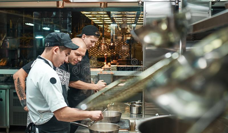 Culinary school. Strict young chef in apron looking carefully how his assistant cooking at restaurant kitchen. Food preparation royalty free stock photos