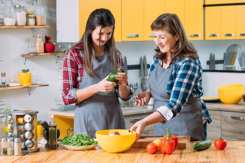 Culinary trend health food du jour family cooking. Culinary trend. Health food du jour. Family cooking. Mother and adult daughter exploring modern vegetarian royalty free stock images
