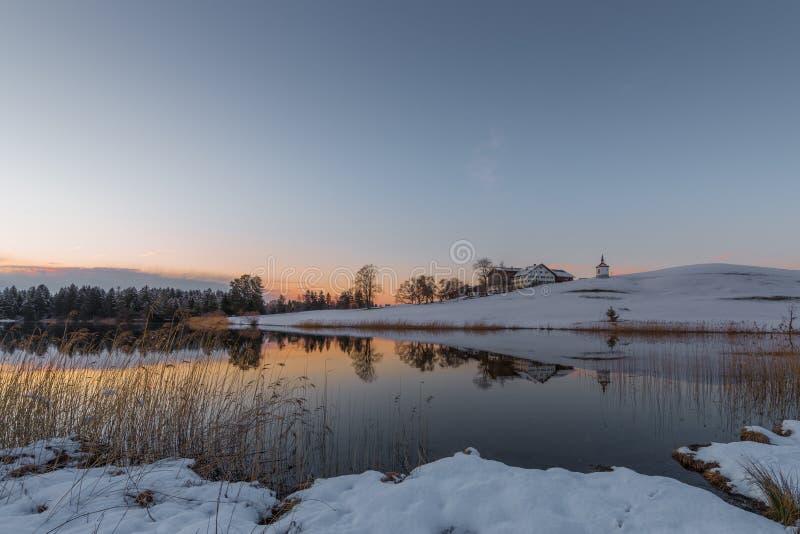 Cultive en la colina en el lago en invierno mientras que cielo anaranjado imágenes de archivo libres de regalías
