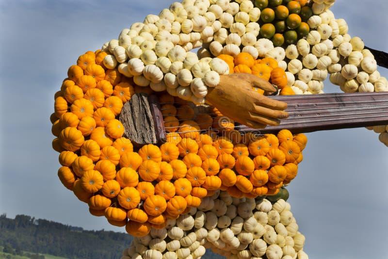 Cultive la guitarra y al guitarrista del arte hechos de pequeña naranja, de verde y de wh imagenes de archivo
