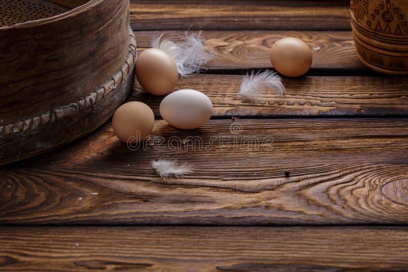 Cultive ovos e penas orgânicos frescos da galinha no fundo de madeira rústico Páscoa imagem de stock royalty free