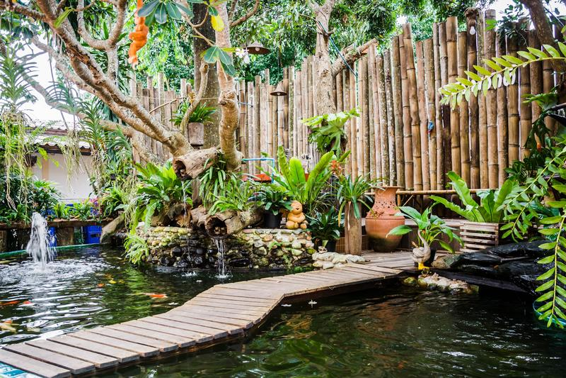 cultive un huerto con la charca de los pescados del koi y de la pared de bambú adornada imagen de archivo