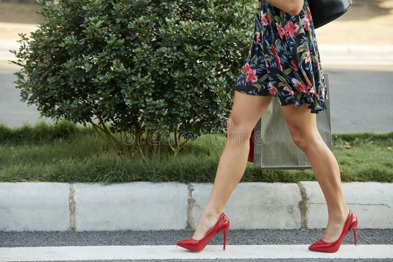 Cultivez la dame avec des sacs en papier marchant sur la route image libre de droits
