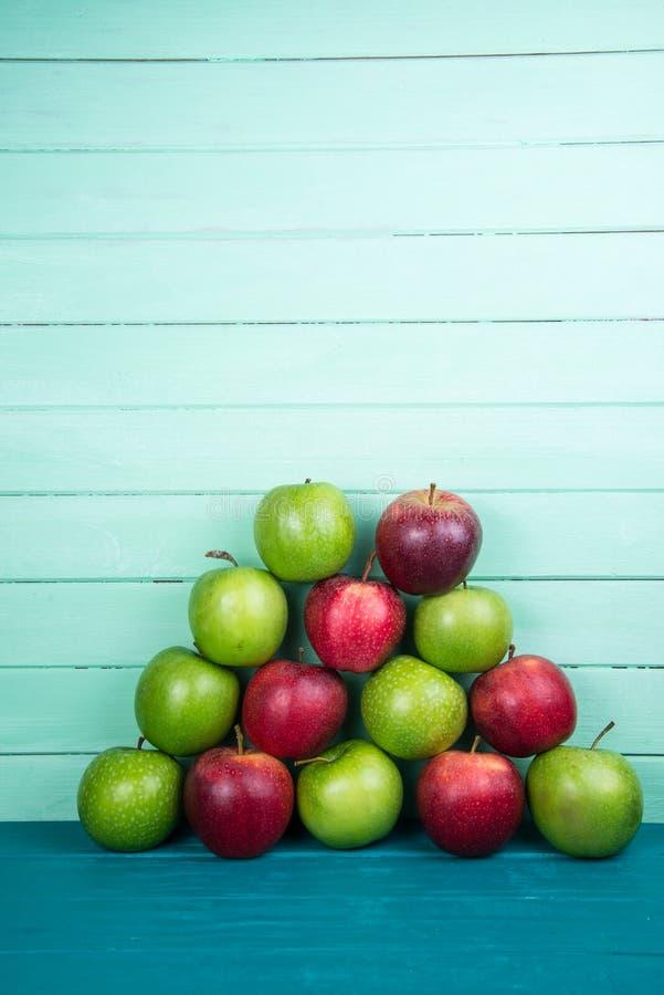 Cultivez la pyramide fraîche de rouge organique et les pommes vertes d'automne courtisent dessus photo stock