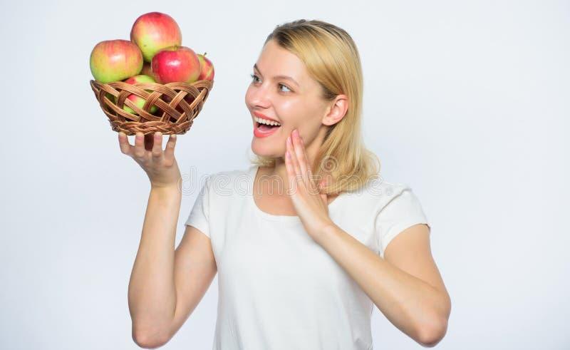 Cultivo de vida verde Alimento sano Mujer feliz que come Apple huerta, muchacha del jardinero con la cesta de la manzana Autumn H foto de archivo libre de regalías
