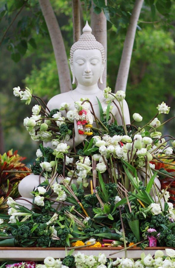 Culto di buddismo con i fiori e la ghirlanda d'offerta alla statua di Buddha fotografia stock