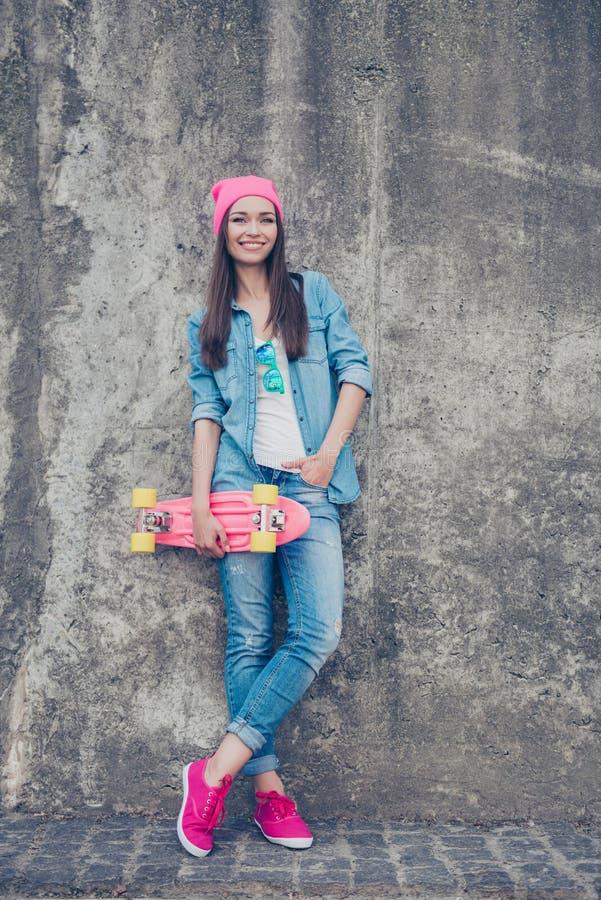Cultura de juventude A menina atrativa nova do moderno está com patim b imagens de stock
