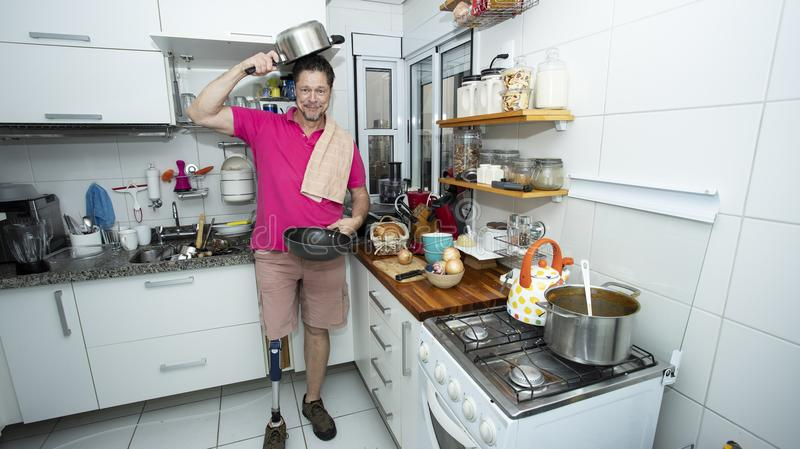 Cultural diversity, handicapped man, cleaning the kitchen stock photography