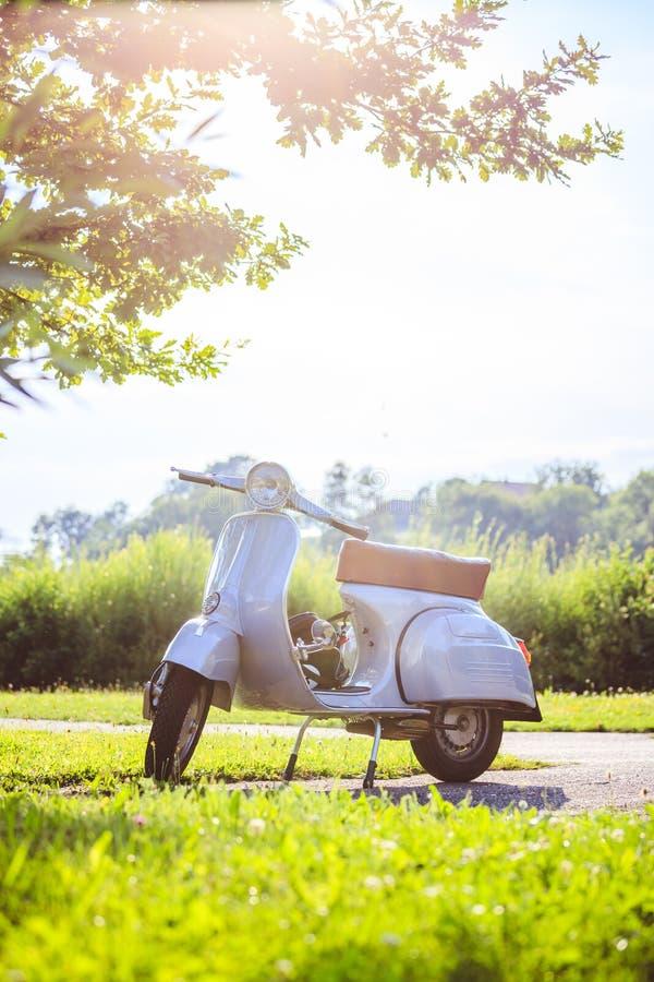 Culture de la jeunesse d'heure d'été : Le scooter bleu se gare sur le pré photos stock